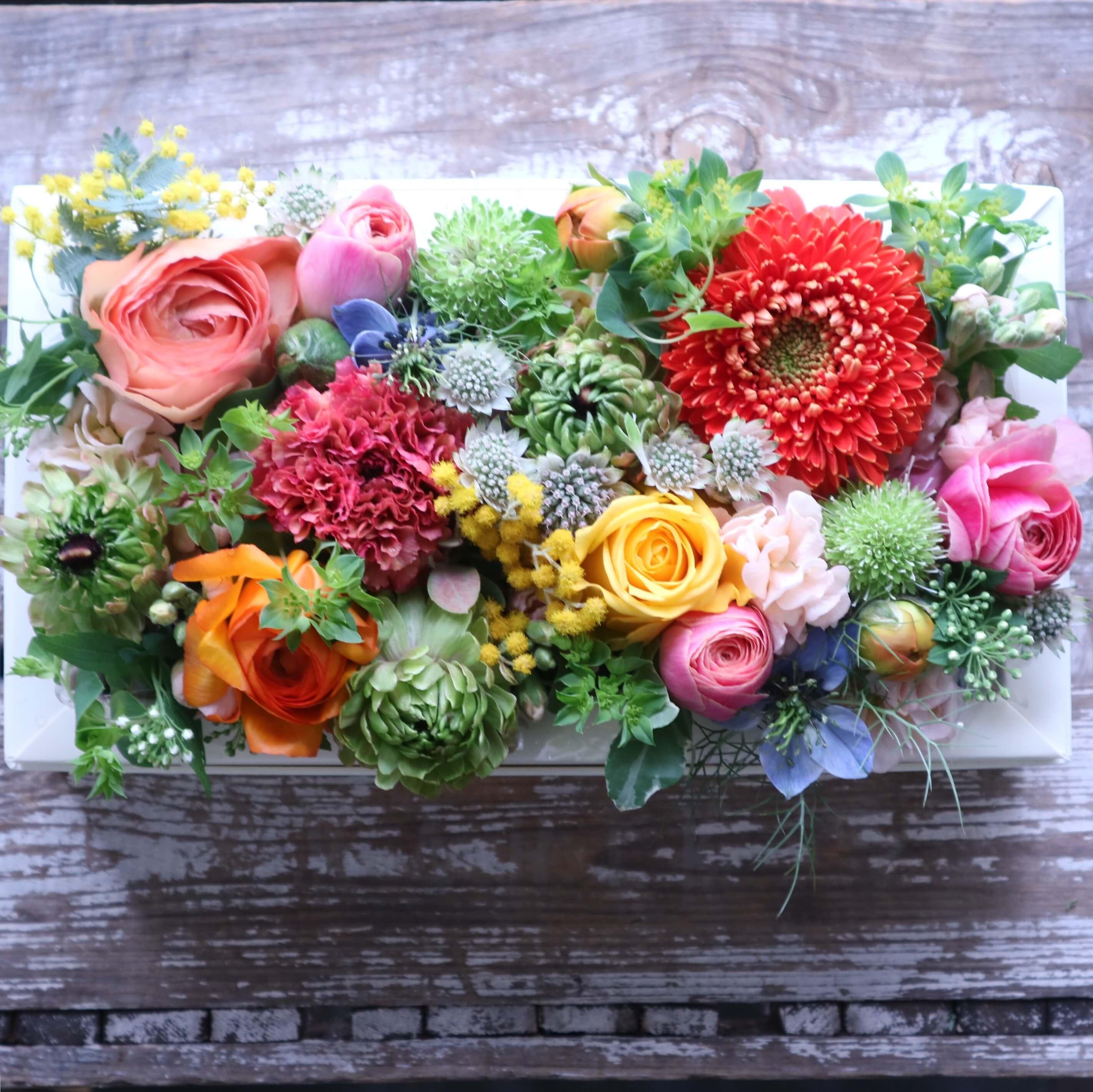 ボックスフラワーアレンジメント 色味:ビタミンカラフルに季節のお花でおまかせ の参考画像です